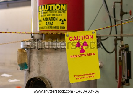 Ionizing radiation hazard symbol, caution radiation area and personnel dosimeter required text on yellow warning sign displayed on the equipment that produces dangerous ionizing radiation