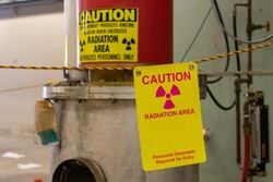 Ionizing radiation hazard symbol, radiation area and personnel dosimeter required text on yellow warning sign displayed on the equipment that produces dangerous ionizing radiation