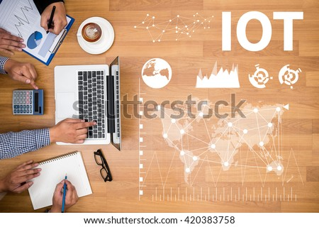 IOT Business team hands at work with financial reports and a laptop