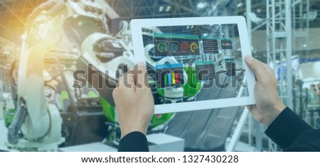 iot industry 4.0 concept,industrial engineer(blurred) using tablet with augmented mixed with virtual reality technology to monitoring machine in real time.Smart factory use Automation robot arm