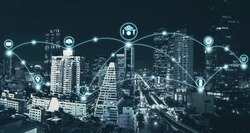 IoT or internet of thing and smart city concept with blue tone night cityscape background.