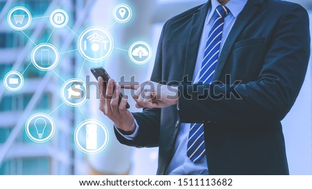 IoT or internet of thing and wifi 6 concept with Young businessman standing and point to phone and IOT icon hologram with cityscape background. #1511113682