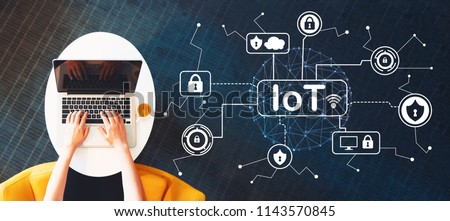 IoT security theme with person using a laptop on a white table