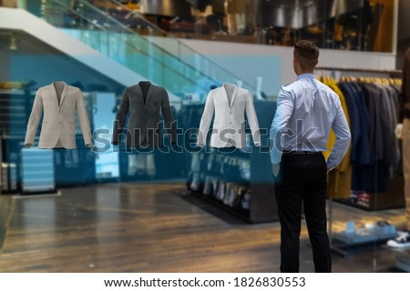 iot smart retail futuristic technology concept, happy man try to use smart display with virtual or augmented reality  in the shop or retail to choose select ,buy cloths and give a rating of products
