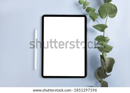 iPad pro with white screen on blue background with apple pencil. flat lay