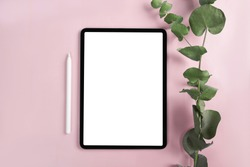 iPad pro with white screen on pink color background. Flatlay. Office background