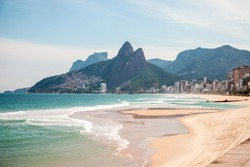 Ipanema Beach, in Rio de Janeiro, Brazil, totally deserted during the pandemic of the new Corona virus. Morro Dois Irmaos with a beautiful blue sky, clear sand and sea with shades of blue and green.