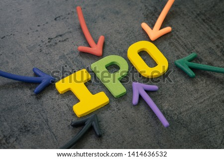 IPO, Initial Public Offering concept, colorful arrows pointing to the word IPO at the center of black cement chalkboard wall, start first sale in stock market issued by a company to the public.