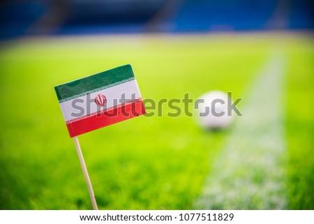 IR IRAN national Flag and football ball on green grass. Fans, support photo, edit space.  #1077511829