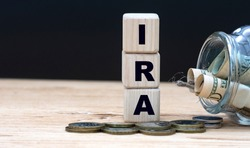 IRA (Individual Retirement Account) - abbreviation on cubes on the background of a capacity with money