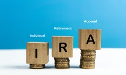 IRA Individual Retirement Account text on wood cube block stack with coins