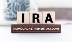 IRA individual retirement account word on wood cube block with blue background.