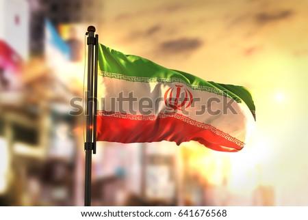 Iran Flag Against City Blurred Background At Sunrise Backlight 3D Rendering Stockfoto ©