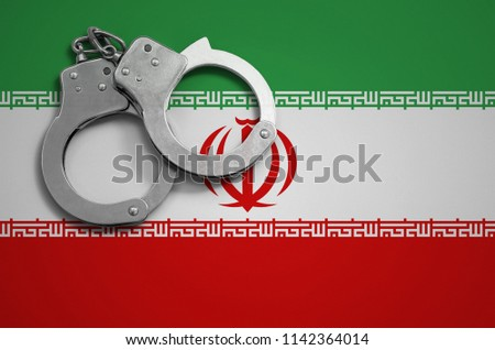 Iran flag  and police handcuffs. The concept of crime and offenses in the country #1142364014