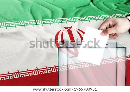 iran flag, iran  the symbol of elections Male hand puts down a white sheet of paper with a mark as a symbol of a ballot paper against the background  Stockfoto ©