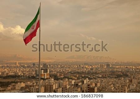 Iran flag waving  in the wind above skyline of Tehran lit by orange glow of sunset. Stockfoto ©