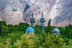 Iran, in the oasis of Rayen ( district of Kerman), In the middle of the desert a beautiful coloured mosque surrounded by green vegetation. The rock mountain in the background. The 24th of April 2018
