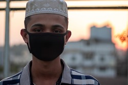 Iran muslim boy with hat going to jummah prayer,wearing face mask to prevent coronavirus.wearing mask can prevent the infection of coronavirus.Coronavirus and Air pollution pm2.5 concept in iran