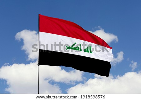 Iraq flag isolated on the blue sky with clipping path. close up waving flag of Iraq. flag symbols of Iraq.