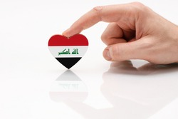 Iraq flag. Love and respect Iran. A man's hand holds a heart in the shape of the Iraqi flag on a white glass surface. The concept of patriotism and pride.