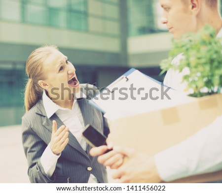 Irate woman is dismissing young manager for violating the job description outdoors.