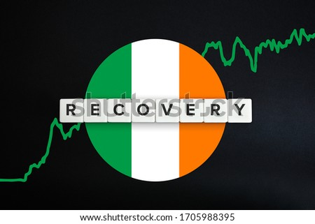 Ireland economy recovery concept. Financial, industrial, business and market sector comeback and upturn. Block letters, irish flag and stock chart on black background.