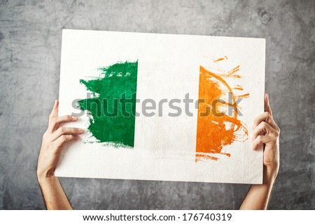 Ireland flag. Man holding banner with Irish Flag. Supporting national team, patriotism concept.