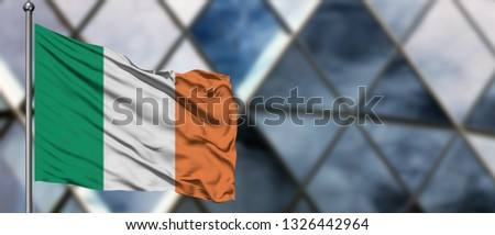 Ireland flag waving in the wind against blurred modern building. Business concept. National cooperation theme. #1326442964