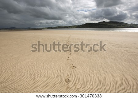 Ireland west coast landscape scene with footprints in rippled  sand during stormy weather in summer on a sandy beach with sun shining through broken cloud.