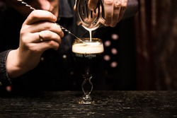 Irish Coffee cups with cream on a dark background, on the bar, warming cocktail, cooking process