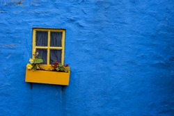 Irish cottage background, window with flower box and blue wall