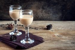 Irish cream coffee liqueur, Christmas decoration and cones over rustic wooden background - homemade festive Christmas alcoholic drink