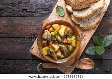 Irish dinner. Beef meat stewed with potatoes, carrots and soda bread on wooden background, top view, copy space. Homemade winter comfort food - slow cooked Сток-фото ©
