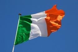 Irish flag fluttering in a brisk breeze against a bright blue sky.