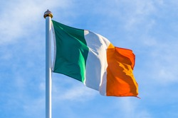 Irish flag waving in the wind in the early morning at sunrise against a blue cloudy sky
