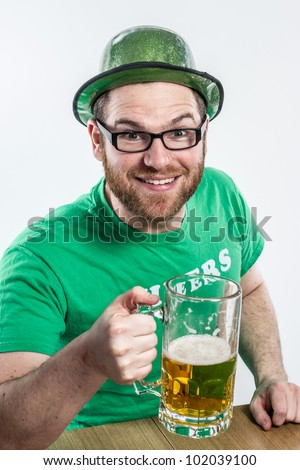 Irish guy in bar red hair glasses green clothes hat toasting to Eire on Saint Patty's day cute young