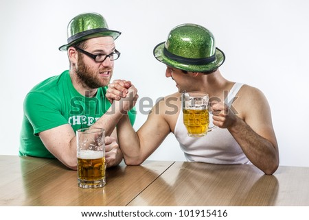 Irish Men arm wrestling in green hats on St. Patty's Day with mugs of frothy beer at local tavern, in white tank top and shirt