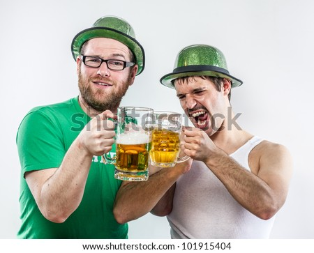 Irish men friends toasting to St. Patrick in green hats on holiday with large glasses of beer at bar, mustache, shirt, and shouting
