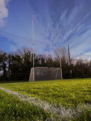 Irish National sport goal posts on a green grass training pitch. Concept practice rugby, hurling, camogie, gaelic football. Blue cloudy sky and dark trees behind goal post.