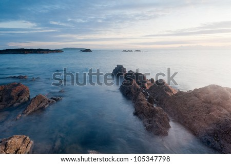 Irish shore photographed at sunrise. Beautiful rocky beach in warm sunlight. Colorful cloudy sky in the background.
