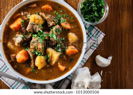 Photo of  Irish stew made with beef, potatoes, carrots and herbs. Traditional  St patrick's day dish. Top view