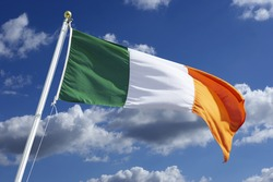IRISH TRICOLOUR NATIONAL FLAG WITH BLUE SKY AND WHITE CLOUDS