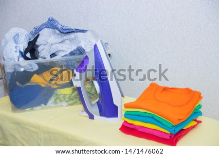 Iron and baby clothes. Colored clothes on an ironing board. Bright t-shirts. Ironed and non-ironed colored children's underwear on the board. Ironing board. A pile of things.