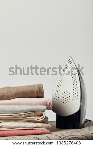 Iron and folded ironed clothes on ironing board isolated on grey #1365278408