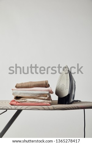Iron and folded ironed clothes on ironing board isolated on grey #1365278417