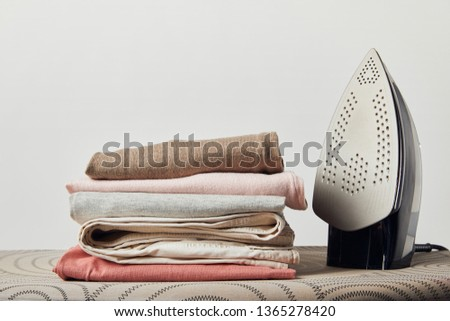 Iron and folded ironed clothes on ironing board isolated on grey #1365278420