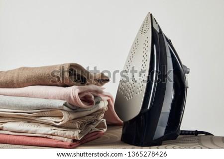 Iron and folded ironed clothes on ironing board isolated on grey #1365278426