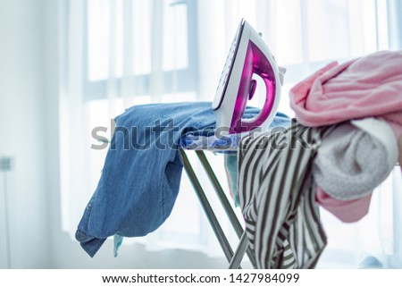 Iron and pile of clean clothes after laundry on ironing board