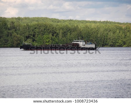 Iron barge and pusher tug boat on River. Large cargo barge transporting iron to main harbor for exporting along river. Tug boat hauls a large barge down river. Tug Boat and Large Barge.