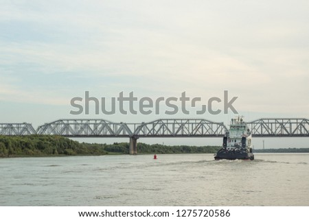 Iron barge and tug boat on River. Large cargo barge transporting iron to main harbor for exporting along river. Tug boat hauls a large barge down river.